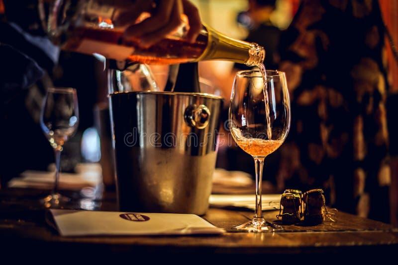 Moscú, Rusia 30 de marzo de 2019: degustación de vinos: Un vidrio de champán rosado se vierte imagenes de archivo