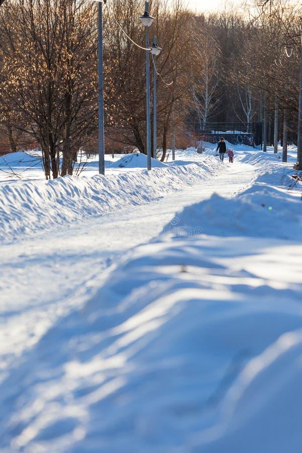 MOSCÚ, RUSIA - 20 DE MARZO DE 2018: Una mujer está caminando con un pequeño niño en un callejón nevado del parque iluminado por l foto de archivo