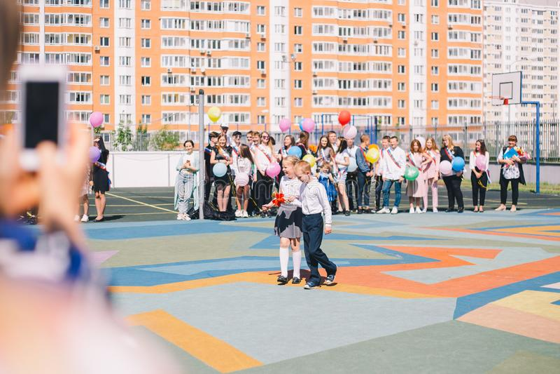Moscú, Rusia - 22 de mayo de 2019: Alumnos muchacho y anillo de la muchacha la campana en la campana y la graduación pasadas fotos de archivo