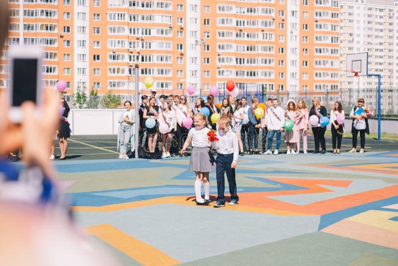 Moscú, Rusia - 22 de mayo de 2019: Alumnos muchacho y anillo de la muchacha la campana en la campana y la graduación pasadas fotografía de archivo libre de regalías
