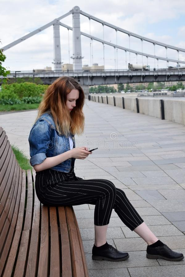 Moscú, Rusia - 13 de mayo de 2019: La mujer joven está mirando en su smartphone en el terraplén de Krymskaya imagen de archivo libre de regalías
