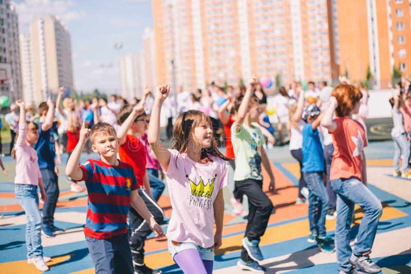 Moscú, Rusia - 22 de mayo de 2019: Niños que bailan en la escuela en un día de fiesta en el patio Foco en muchacha imagen de archivo