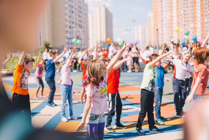 Moscú, Rusia - 22 de mayo de 2019: Niños que bailan en la escuela en un día de fiesta en el patio Foco en muchacha fotos de archivo