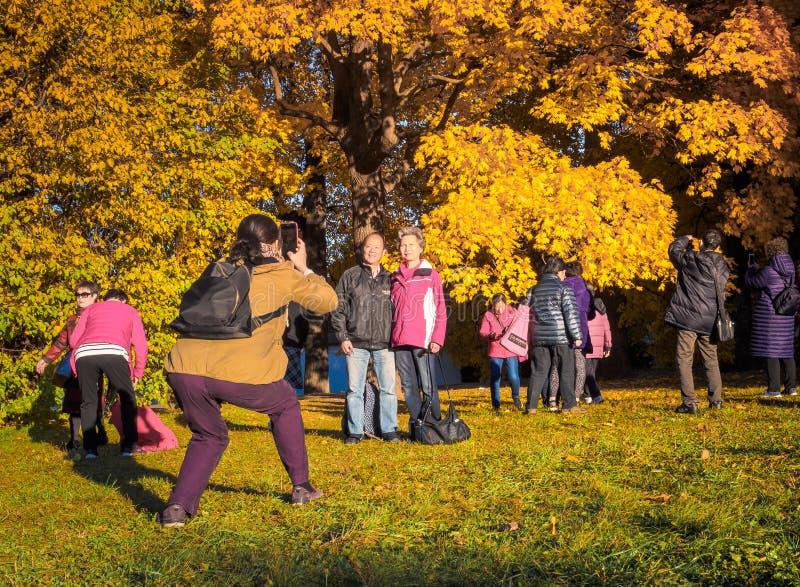 Moscú, Rusia - 11 de octubre de 2018: Los turistas chinos caminan el parque del otoño La gente asiática toma imágenes en el fondo imagen de archivo libre de regalías