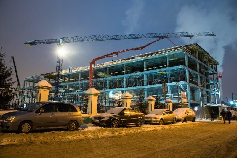 MOSCÚ, RUSIA, DICIEMBRE, 27 2018: Grúa de construcción y la construcción del edificio moderno Trabajo nocturno en el emplazamient imagen de archivo libre de regalías