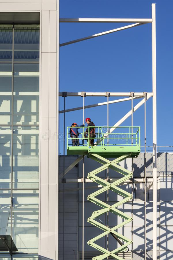 Moscú, Rusia, el 2 de abril de 2019 Los trabajadores de la instalación están trabajando en la plataforma de elevación delante de  imagen de archivo