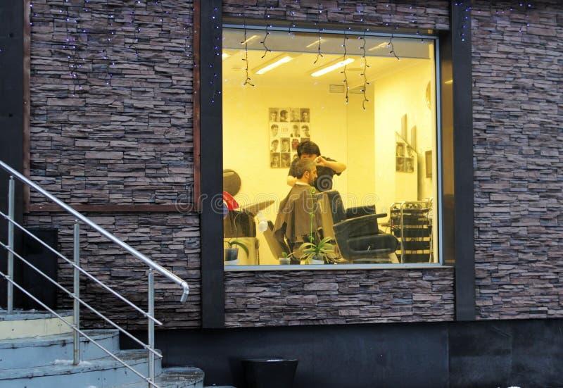 Moscú, Rusia, 12 12 2018, el peluquero principal corta al hombre, la visión a través de la ventana imagen de archivo libre de regalías