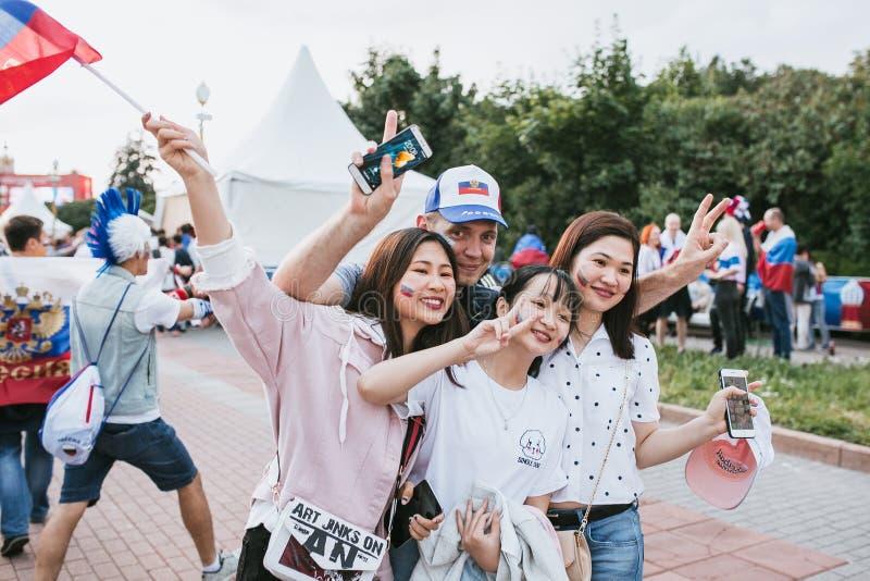 MOSCÚ, RUSIA - JULIO DE 2018: El fanático del fútbol ruso se fotografía con los coreanos durante el mundial fotos de archivo