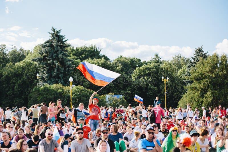 MOSCÚ, RUSIA - JUNIO DE 2018: Un fanático del fútbol agita una bandera nacional rusa en una muchedumbre en la zona de la fan dura imagenes de archivo
