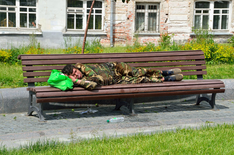 Moscú, Rusia, junio, 12, 2017, hombre sin hogar que duerme en un banco en el cuadrado de Khitrovskaya en el verano en Moscú imagenes de archivo