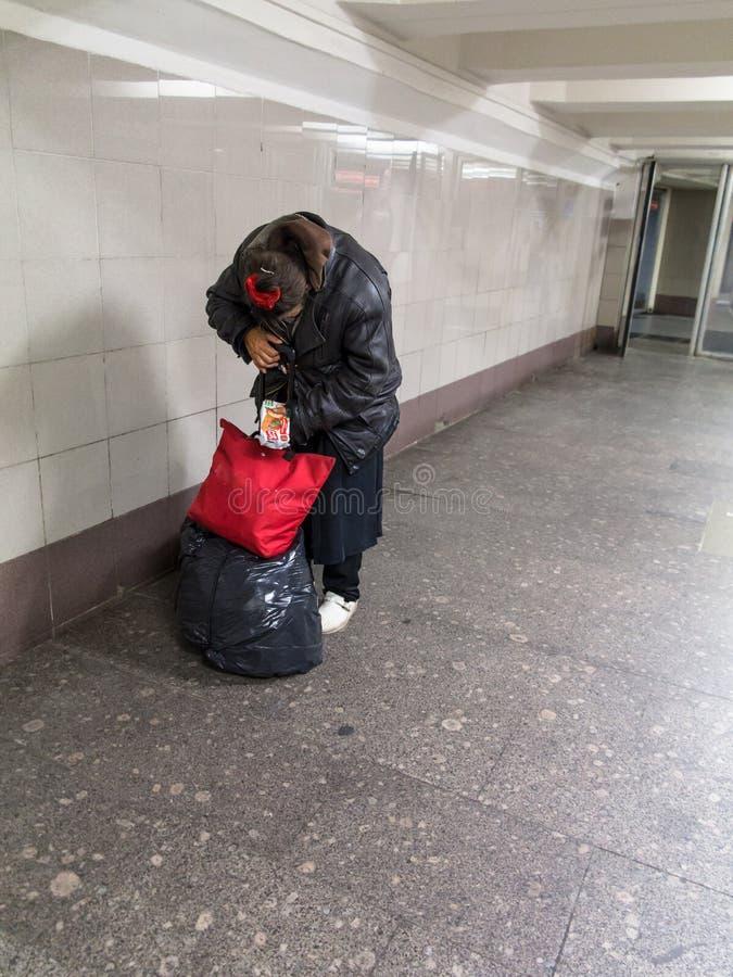 Moscú, Rusia - 9/20/2015: La señora sin hogar está ocultando su cara que finge clasificar el paquete entre el ferrocarril de Leni imagenes de archivo