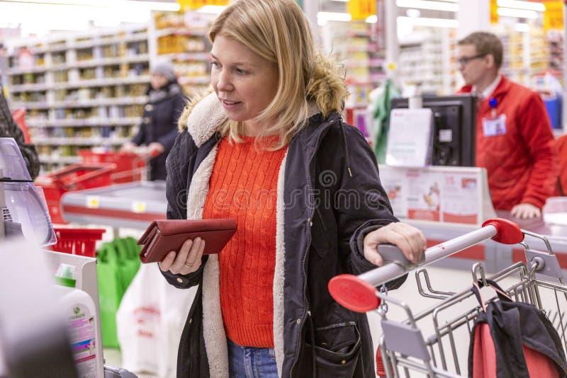 Moscú, Rusia, 11/22/2018 Mujer joven que paga compras en el pago y envío foto de archivo libre de regalías