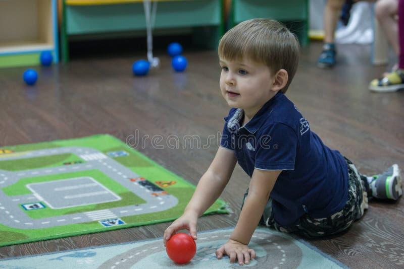 2019 01 22, Moscú, Rusia Niño pequeño lindo que se sienta en la alfombra en el jardín del niño imagen de archivo libre de regalías