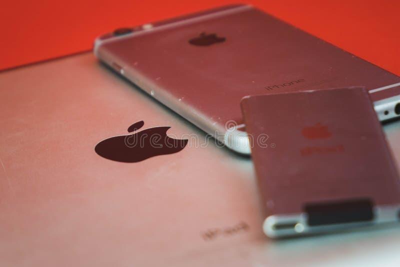 Mosc?, Rusia - 25 DE ABRIL DE 2019: iPod, iphone e ipad mintiendo en fila Producci?n en fondo rojo Productos de Apple Producido c imagen de archivo