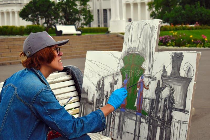 Mosc?, Rusia 08 02 2019 El artista de la mujer dibuja en la calle las pinturas de aceite constructivas foto de archivo