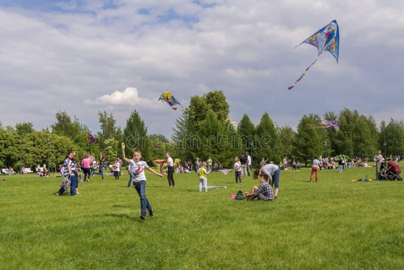 mosc? Rusia 26 pueden 2019 La gente se relaja en un c?sped grande en el parque Tsaritsyno Lanzamiento en las cometas coloridas de imágenes de archivo libres de regalías