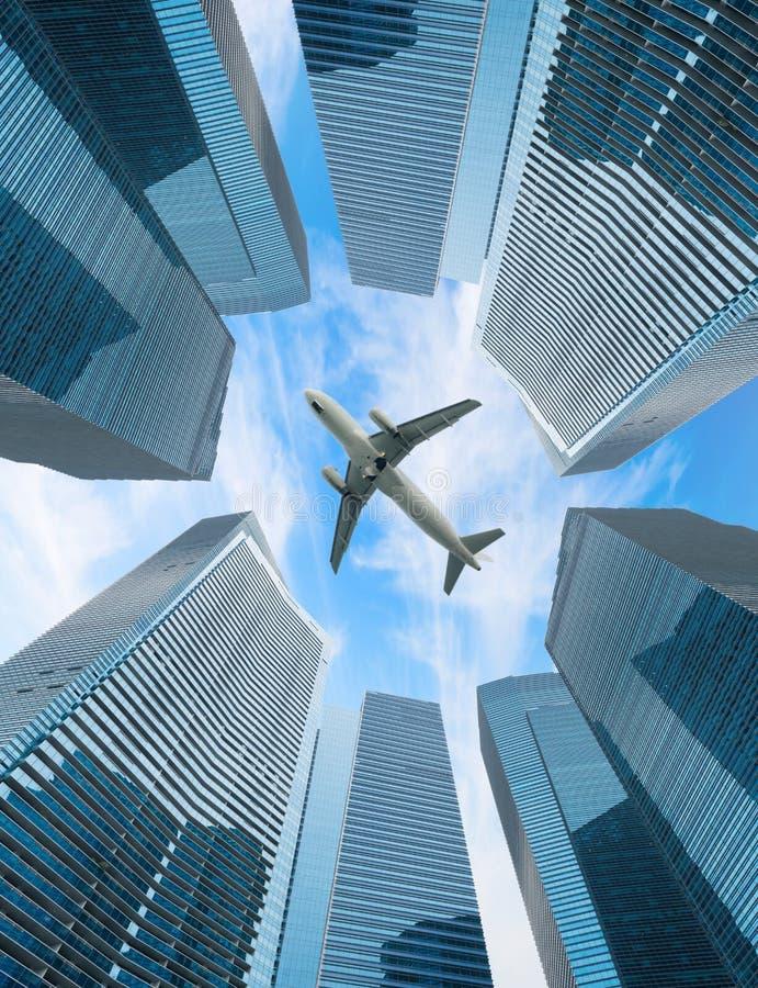 Mosca blanca del aeroplano sobre ciudad moderna fotos de archivo