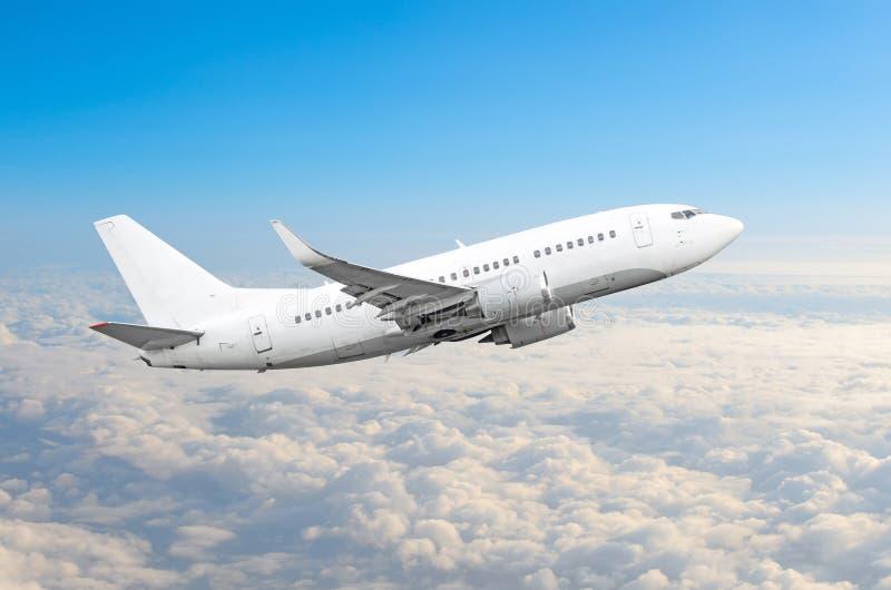 Mosca del aeroplano del pasajero en una altura sobre las nubes cubiertas y el cielo azul foto de archivo