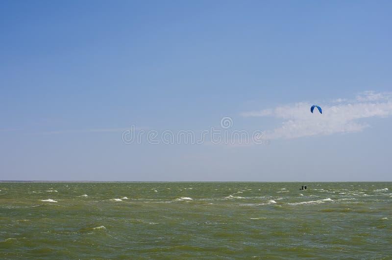 Mosca del ala flexible durante día de verano soleado de la playa del mar del paragliding asombroso del paisaje fotografía de archivo