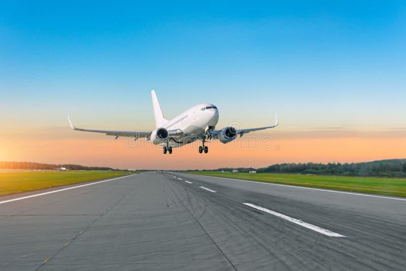 Mosca del avión de pasajeros para arriba encima sacar la pista del aeropuerto en la puesta del sol imagen de archivo libre de regalías