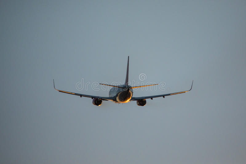 Mosca del avión de pasajeros para arriba sobre pista del despegue del aeropuerto en la puesta del sol Salida plana del aeropuerto fotografía de archivo libre de regalías