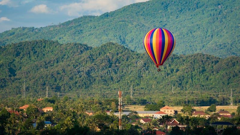 Mosca do balão de ar quente de Colorfull sobre a vila foto de stock