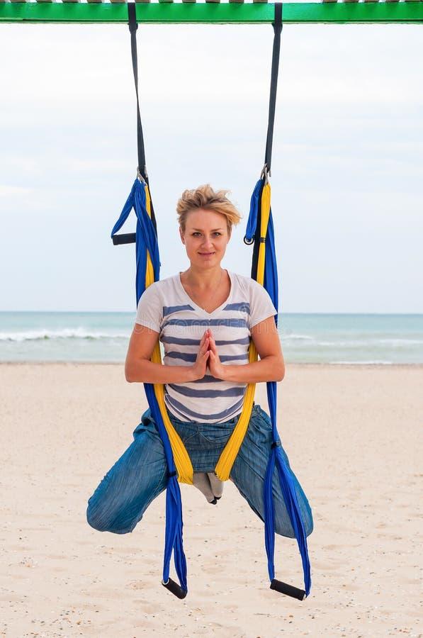 Mosca-ioga, anti gravidade ou ioga da mosca na praia Jovem mulher que faz o exercício das iogas Ioga com a rede pelo mar pose fotos de stock