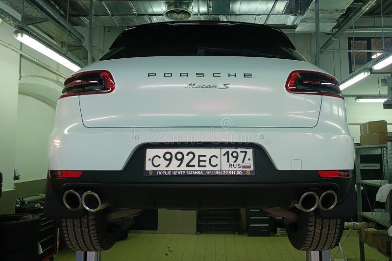 Mosca, Russia - 29 aprile 2019: Porsche bianco Macan S sul distributore di benzina Tiro e ruota che cambiano una riparazione fotografie stock libere da diritti