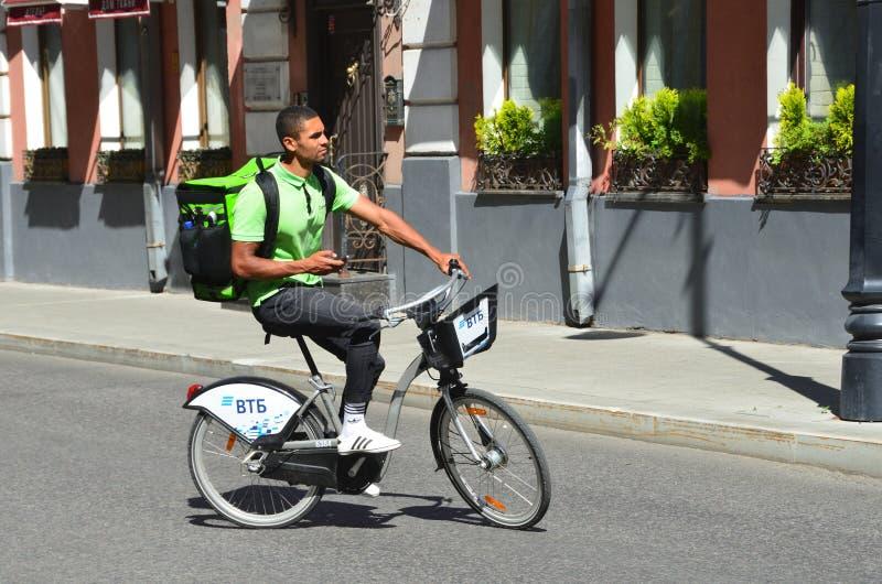 Mosca, Russia, augusta, 12, 2018 Il corriere del club della consegna consegna l'alimento su una bicicletta a Mosca fotografia stock