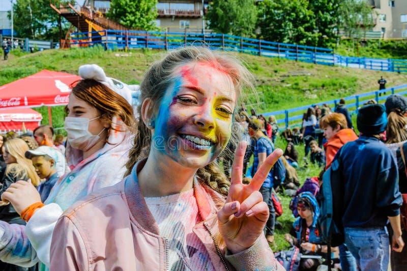 Mosca, Russia - 3 giugno 2017: L'adolescente con i ganci e le trecce, in pittura multicolore, mostra un gesto della vittoria immagini stock