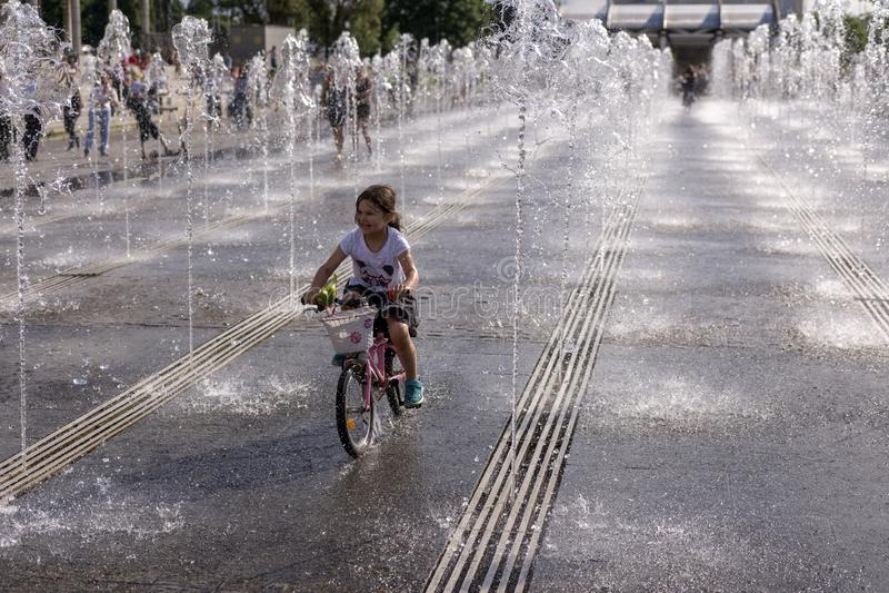 Mosca, Russia, il 2 giugno 2019 Art Museum Park, una bambina che guida una bici in una fontana aperta fotografia stock libera da diritti