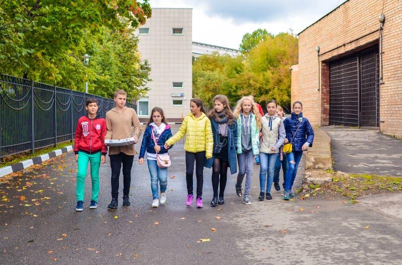 Mosca, Russia, il 23 settembre 2018 Gruppo di giovani ragazzi e di ragazze che parlano e che camminano giù la strada fotografia stock libera da diritti