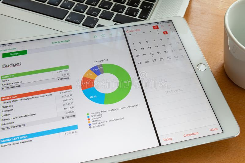 Mosca/Russia - 2 marzo 2019: Il ipad bianco si trova sulla tastiera del macbook, sullo schermo del diagramma Vicino è una tazza immagine stock libera da diritti