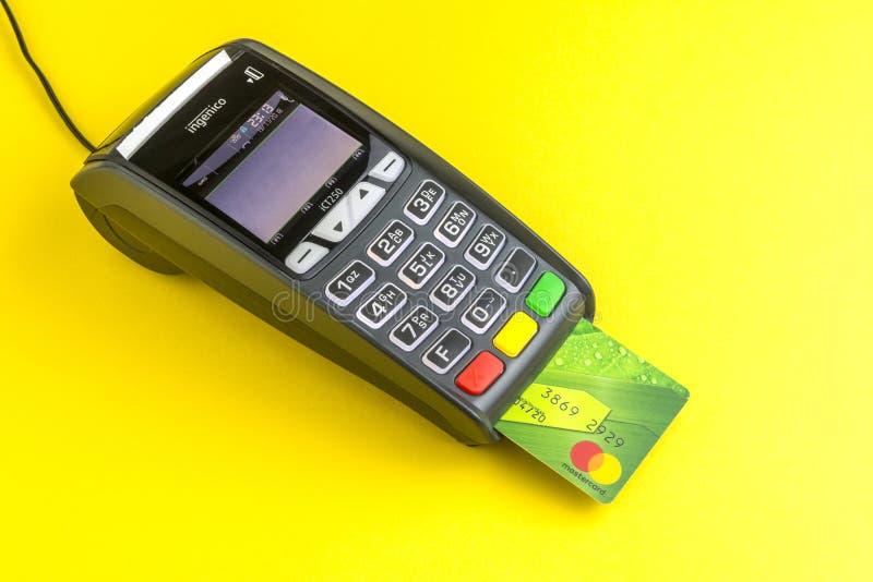Mosca, Russia, 13 11 2018 Terminale di pagamento con carta di credito su fondo giallo Carta di plastica verde Mastercard inserita fotografia stock