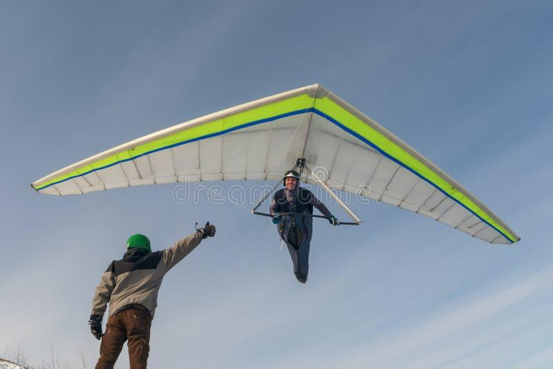 Mosca sonriente del piloto de planeador de caída con su punto bajo del ala sobre la tierra fotos de archivo libres de regalías