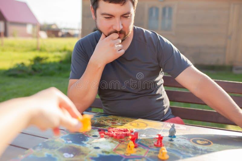 Moscou 18 de junho de 2018 Dois jogadores que jogam o wargame: robôs e miniaturas dos heróis no campo do jogo de mesa fotografia de stock