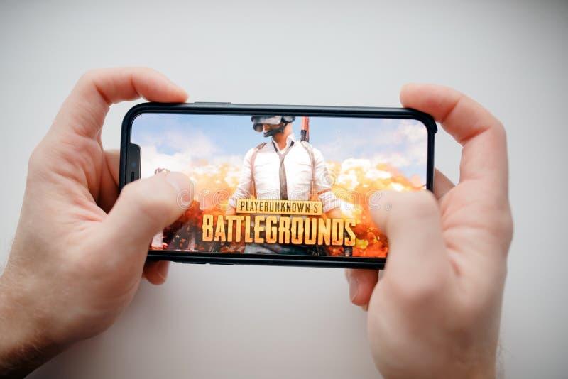 Moscou, Rússia - 1º de janeiro de 2019: Smartphone da terra arrendada do homem com jogo de tiro em linha desconhecido do campo de fotografia de stock