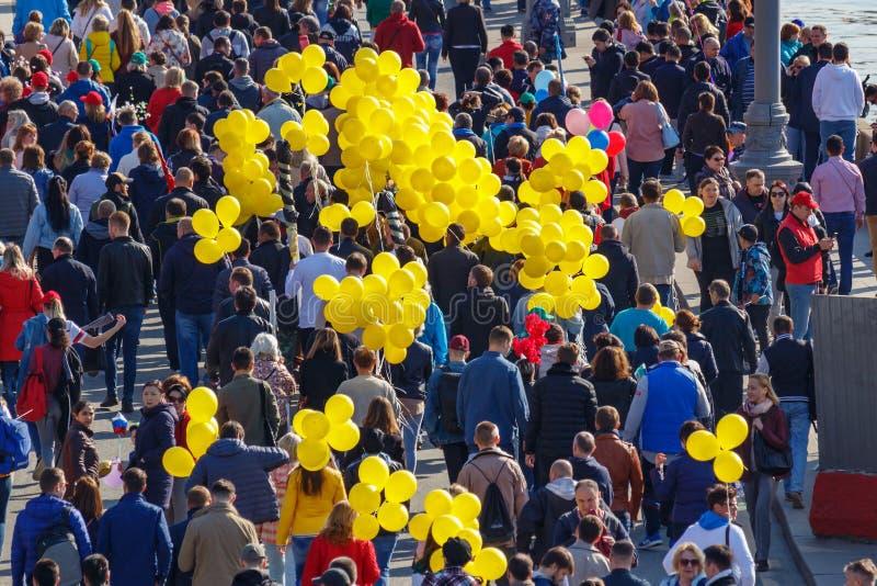 Moscou, Rússia - 1º de maio de 2019: Povos com os balões amarelos na terraplenagem de Kremlevskaya r imagens de stock