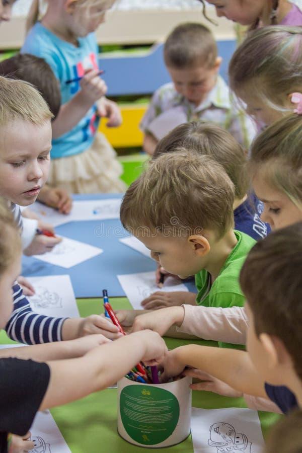 2019 01 22, Moscou, Rússia Crianças que tiram em torno da tabela no jardim da criança fotografia de stock royalty free
