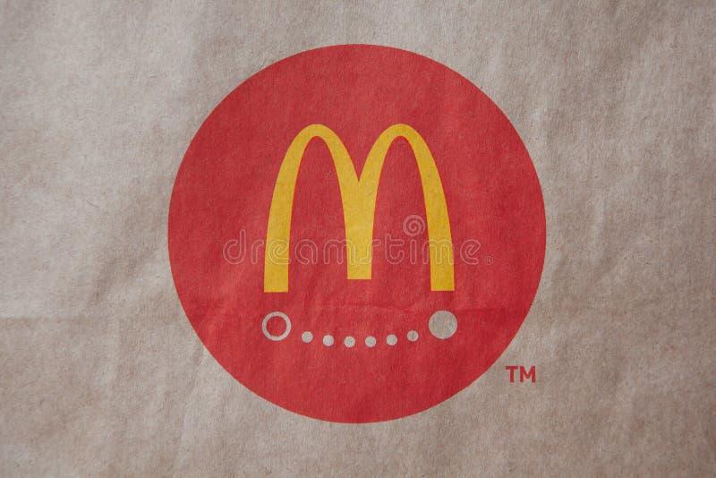 Moscou, Rússia - 6 de abril de 2019: Entrega do alimento do logotipo de mcdonald no fundo marrom do papel do ofício Close-up Vist fotos de stock