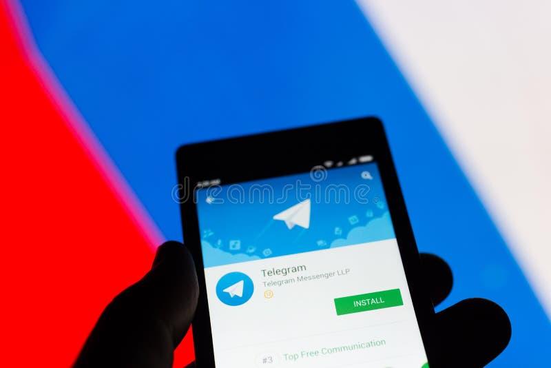 MOSCOU, RÚSSIA - 17 DE ABRIL DE 2018: Um telefone celular na mão com a aplicação do telegrama na loja do jogo de Google Bandeira  fotografia de stock