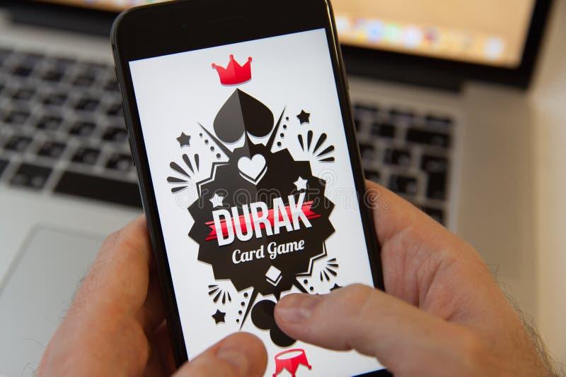 Moscou/Rússia - 20 de fevereiro de 2019: guardando um iPhone no fundo de MacBook tolo do jogo de cartas da poupança de tela fotos de stock