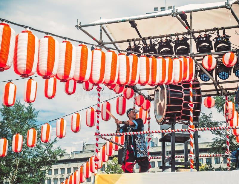 Moscou, Rússia - 16 de julho de 2017: Jogo que dos músicos ASKA-GUMI o taiko rufa no yagura da cena durante o festival japonês Ve imagens de stock