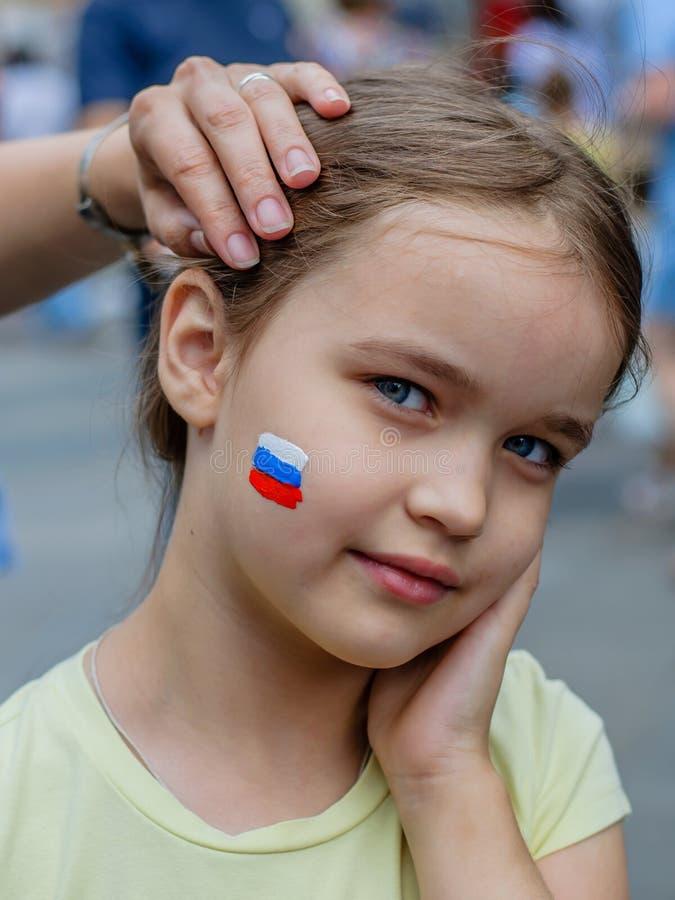 Moscou, Rússia - 7 de julho de 2018: a menina europeia nova com o russo tricolor no mordente, pintura patriótica da cara, ventila fotografia de stock royalty free