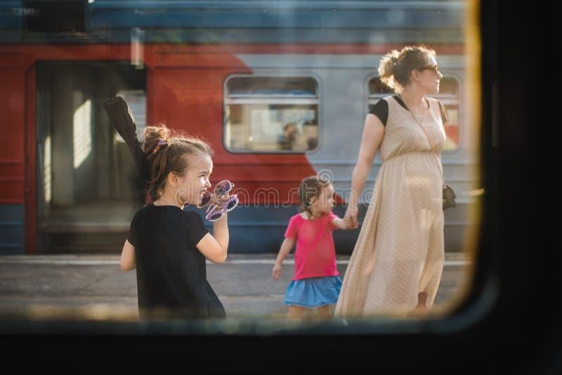 MOSCOU RÚSSIA - 27 de julho de 2017 Vista através da janela do trem família da mamã e das duas filhas, uma de quem mamã guarda pe foto de stock