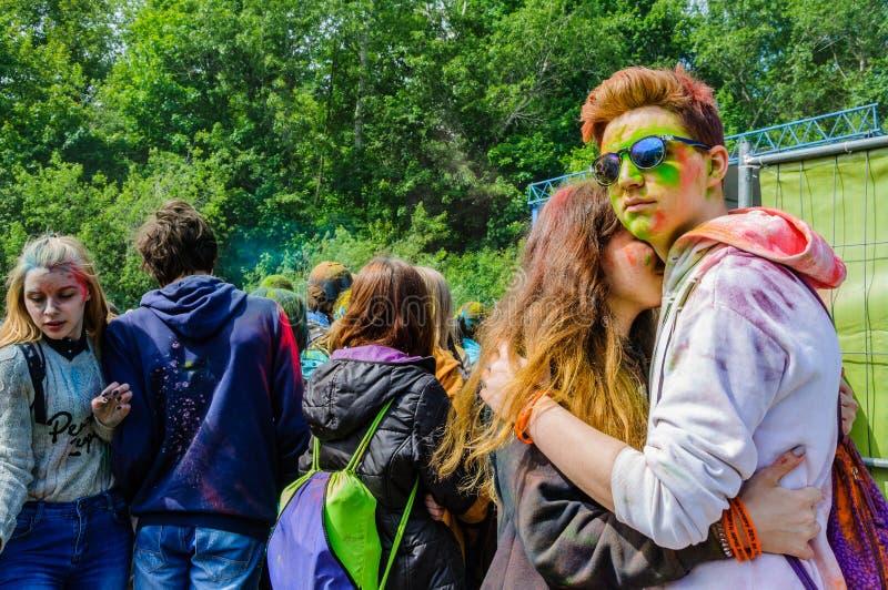 Moscou, Rússia - 3 de junho de 2017: Menino e menina, manchados com pintura, abraço no festival do verão das cores Holi fotografia de stock