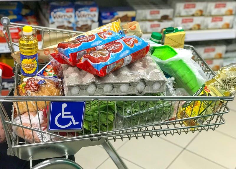 MOSCOU, RÚSSIA - 10 DE JUNHO DE 2019: Homem deficiente que usa uma cadeira de rodas com um carro de Shooping no supermercado de A foto de stock royalty free