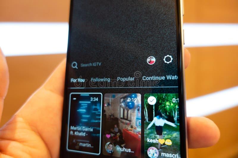 Moscou, Rússia - 23 de junho de 2018: Instagram IGTV O homem pressiona o telefone IGTV do botão Close up do ícone IGTV editorial imagem de stock royalty free