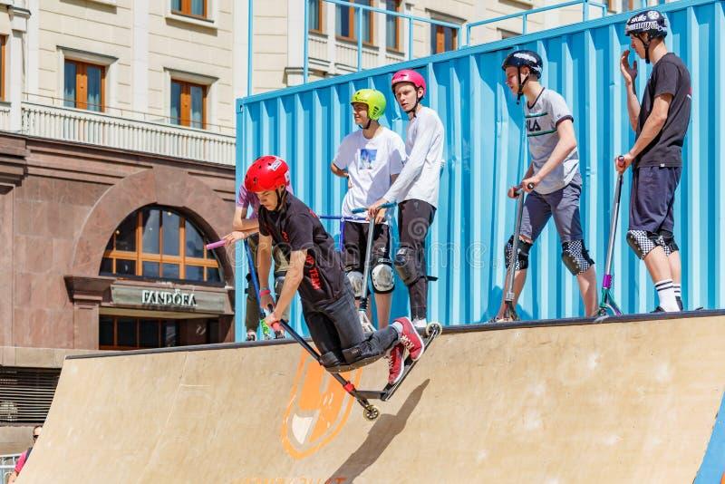 Moscou, Rússia - 2 de junho de 2019: Os cavaleiros novos do flatland em 'trotinette's dos esportes executam truques na rampa no q imagem de stock royalty free