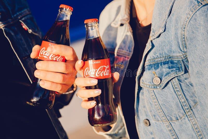 Moscou, Rússia - 27 de junho de 2019: Pares do homem e da menina na garrafa de vidro nas mãos, por do sol de Coca Cola da bebida  fotos de stock royalty free